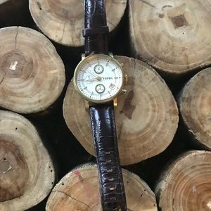 Gold fossil watch with brown leather band.